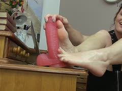 Woman's feet fuck a rubber cock